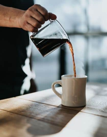 pouring brewed coffee in cup